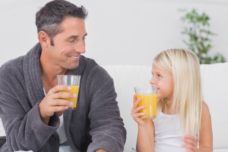 Father and his daughter drinking glass of orange juice on a sofa photo