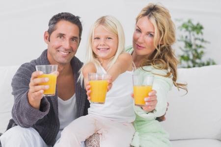 Family holding glasses of orange juice on a sofa photo