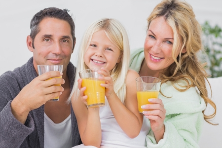 Family drinking glasses of orange juice in the living room photo
