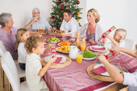 Family having christmas dinner together at table in kitchen photo