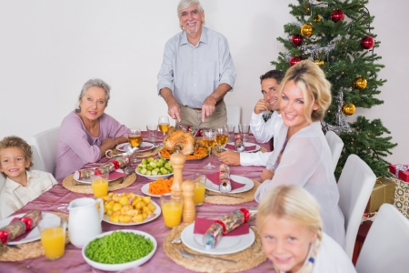 Happy family at christmas dinner with grandfather carving the turkey photo