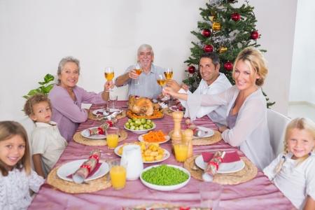 Family raising their glasses at christmas at dinner photo