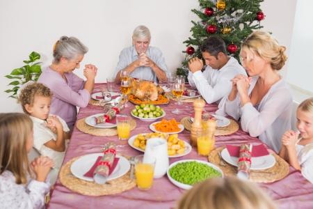 familia orando: Familia dar gracias juntos antes de la cena de Navidad