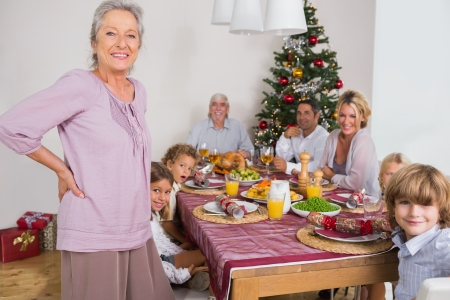 Smiling grandmother standing beside dinner table at christmas photo