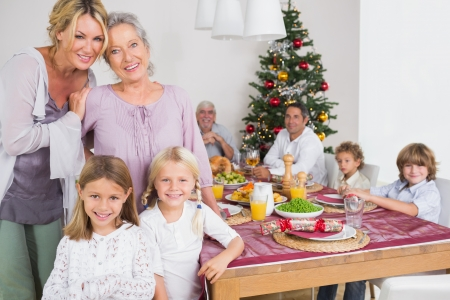 Three generations of women standing by the dinner table at christmas time photo