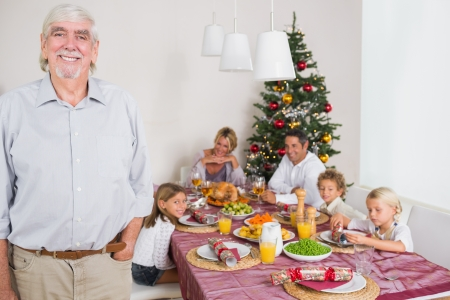 Smiling grandfather standing at the dinner table at christmas photo