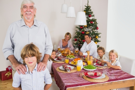 Grandfather and grandson standing beside the dinner table at christmas time photo