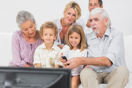 Family watching tv together against a white background photo