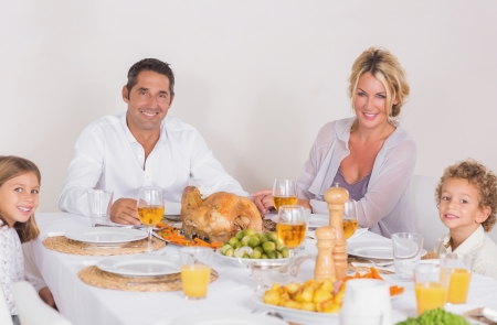 Family sitting on table to eat a turkey photo