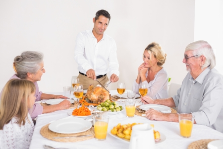 Man cutting slices of turkey for family dinner photo