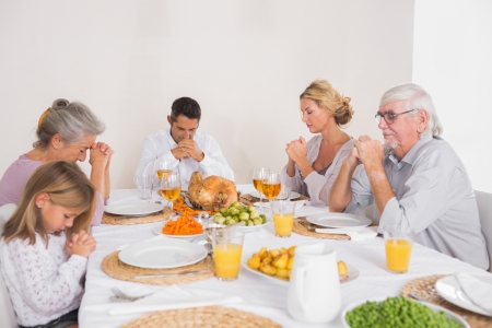 Family saying grace before eating a turkey for dinner photo