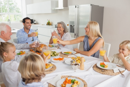 Smiling family raising their glasses together in the kitchen photo