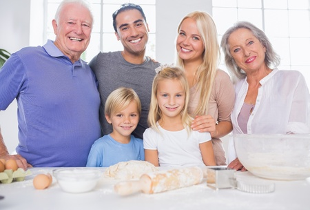 Family posing in the kitchen in front of kitchen utensils photo