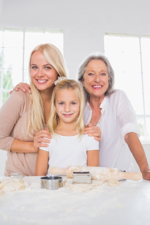 Smiling mothers and daughters cooking together in the kitchen photo