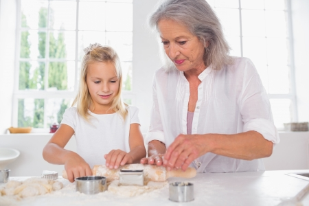 Grandmother and granddaughter making biscuits together photo