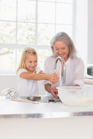 domiciles: Happy grandmother and granddaughter washing hands in the kitchen Stock Photo