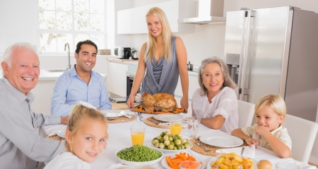 thanksgiving adult: Happy mother serving a turkey for thanksgiving