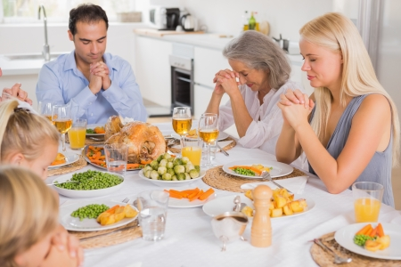 family praying: Familia rezando antes de la cena de Acción de Gracias