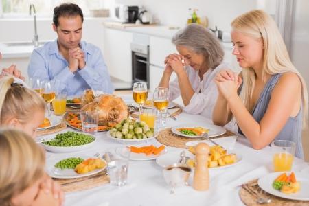 thanksgiving adult: Family praying before thanksgiving dinner
