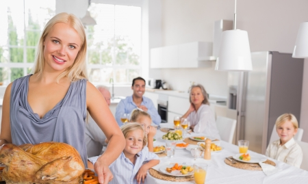 Blonde woman showing the roast turkey with her family behind her photo