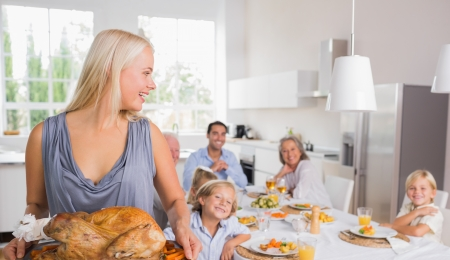 Woman looking her family and holding a turkey photo