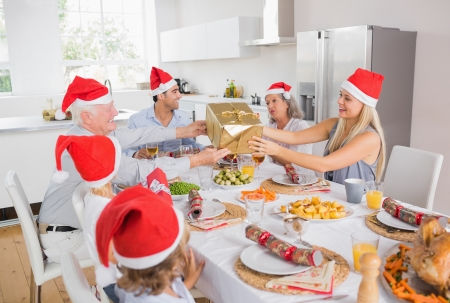 domiciles: Festive family exchanging gifts at christmas at the dinner table
