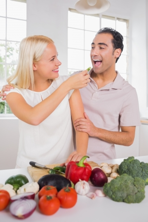 Wife giving vegetable to her husband to taste photo