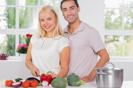 Blonde woman cooking with her husband in the kitchen photo