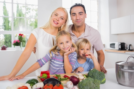 Posing family cutting vegetables together photo