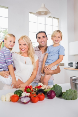 Smiling parents bearing their offspring in the kitchen photo