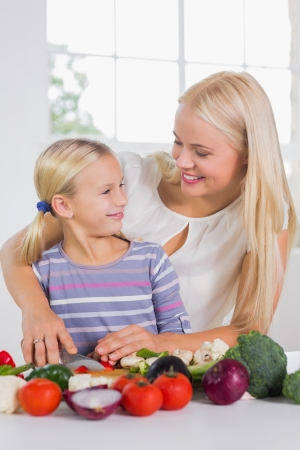 Mother teaching cutting vegetables to her daughter photo