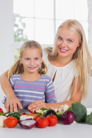 Smiling mother teaching cutting vegetables in the kitchen photo