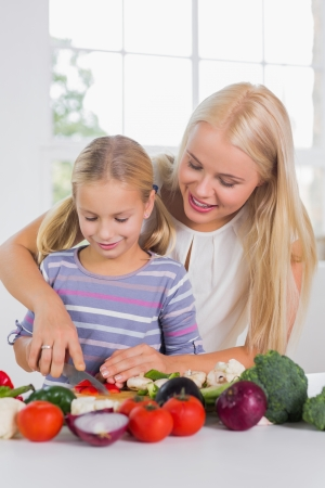 Focused mother teaching cutting vegetables to her daughter photo