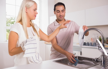 Couple washing dishes together in the kitchen photo