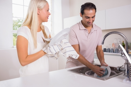 Happy couple washing dishes together photo