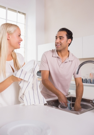 Talking couple washing dishes together in the kitchen photo