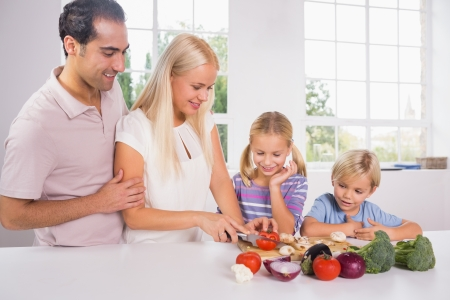 Family cutting vegetables together in the kitchen photo