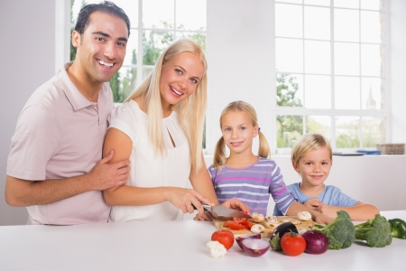 Smiling family cutting vegetables together in the kitchen photo