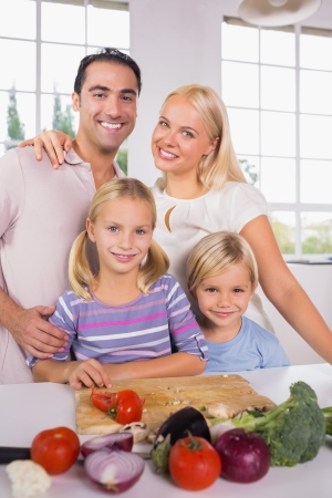 Posing family cutting vegetables together in the kitchen photo