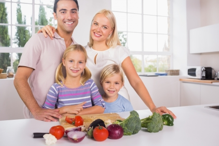 Smiling posing family cutting vegetables together in the kitchen photo