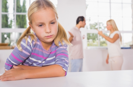 Little girl looking sad in front of fighting parents in the kitchen photo