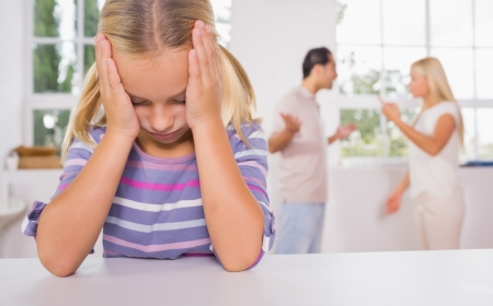 divorce: Little girl looking depressed in front of fighting parents in the kitchen