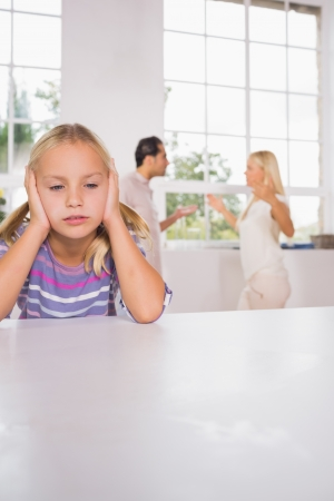 Girl looking despressed in front of fighting parents in the kitchen photo