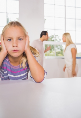 exasperated: Sad girl with fighting parents in the kitchen Stock Photo