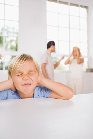Little boy looking sad cause of parents fighting photo