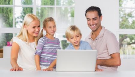 Familia usando una computadora portátil juntos en la cocina