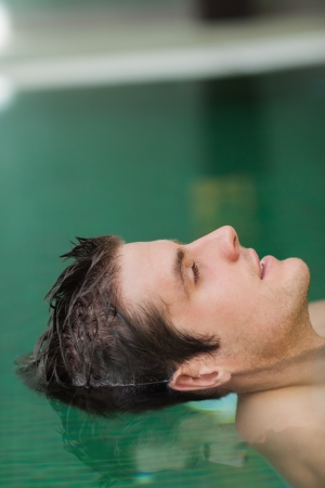 Relaxed handsome man floating in pool photo