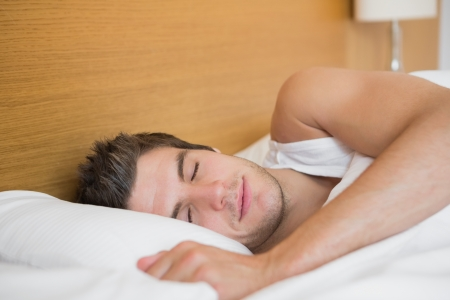 Handsome man asleep in hotel room Stock Photo - 18108318