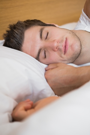 pillow sleep: Man asleep in bed in hotel room Stock Photo
