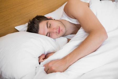 gente durmiendo: Dormir masculino hermoso en la cama en una habitaci�n de hotel Foto de archivo